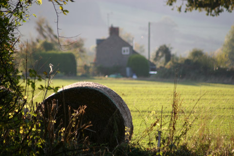 Photo of hay bale in front of rural cottage